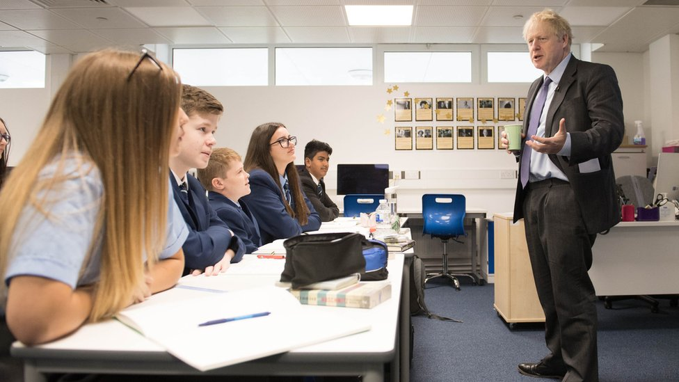 Boris Johnson holds a cup of coffee while speaking in front of a class of students