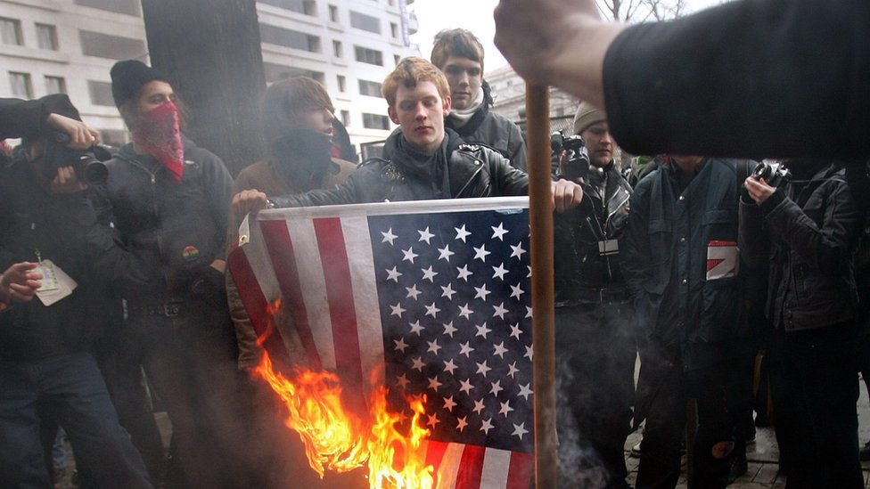 Anarchists burn the US flag after George W Bush's second-term inauguration in 2005