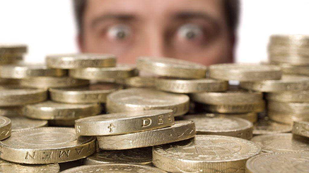 Hombre mirando monedas de libras esterlinas