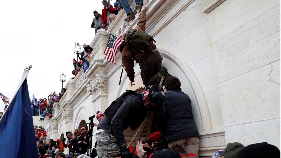 Simpatizantes de Trump escalando los muros del Capitolio