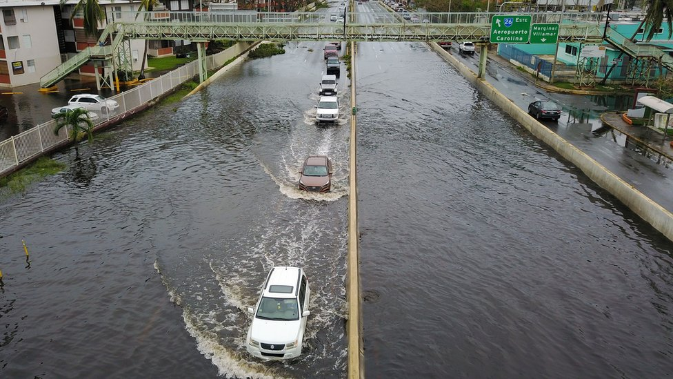 Image shows cars driving through a flooded road in the aftermath of Hurricane Maria in San Juan, Puerto Rico on 21 September 2017