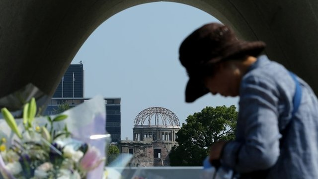 An elderly woman prays front of the monument for atomic bomb victims at the Hiroshima Peace Memorial Park