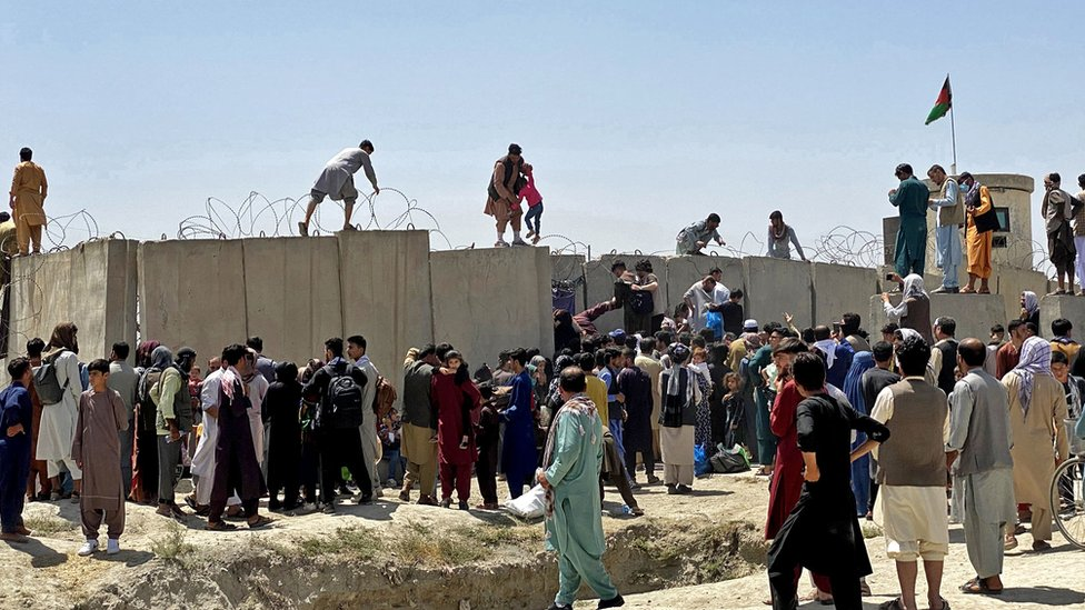 People struggle to cross the boundary wall of Hamid Karzai International Airport to flee Afghanistan