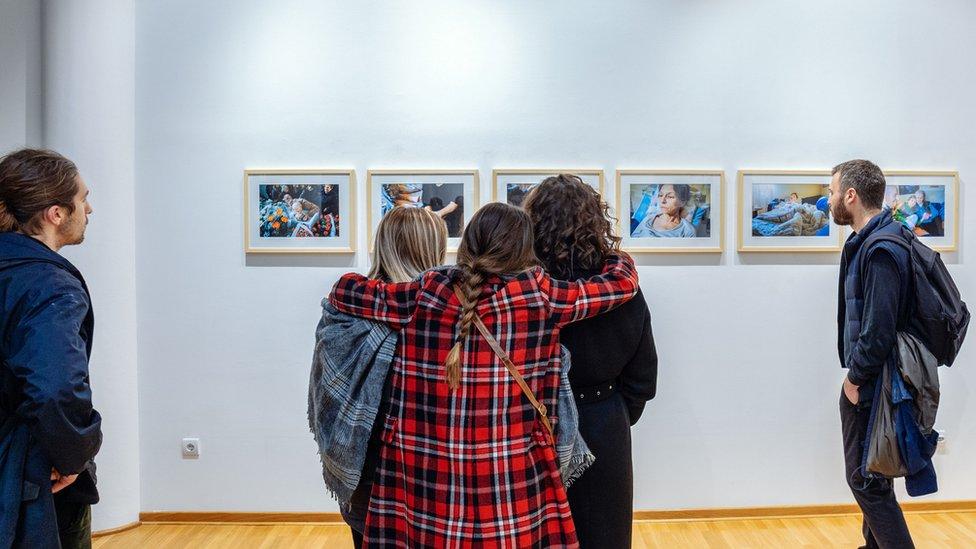 Devojke zagrljene posmatraju fotografije na izložbi