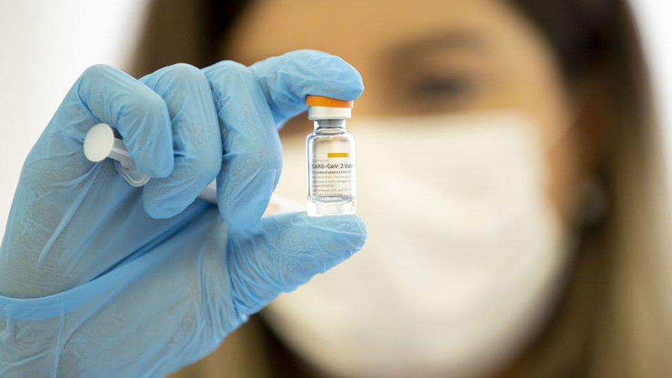 Mujer sosteniendo la vacuna china Coronavac.