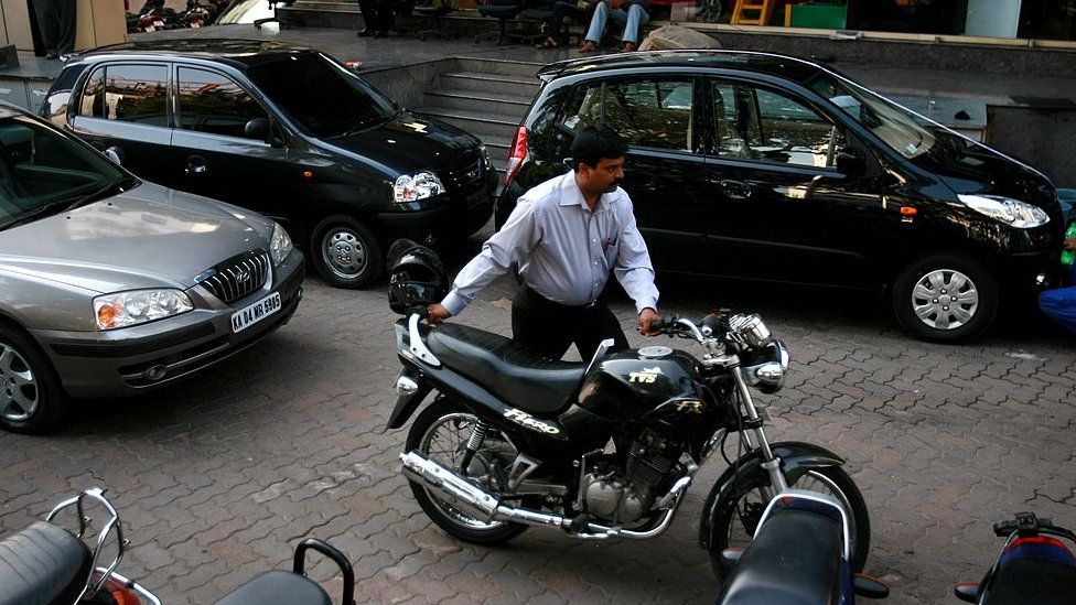 A man pushes his motorbike out of a car dealership, on April 14, 2008 in Bangalore, India.