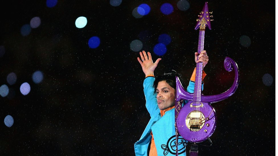 Prince holds a guitar shaped like the symbol that he took as his name in 1993