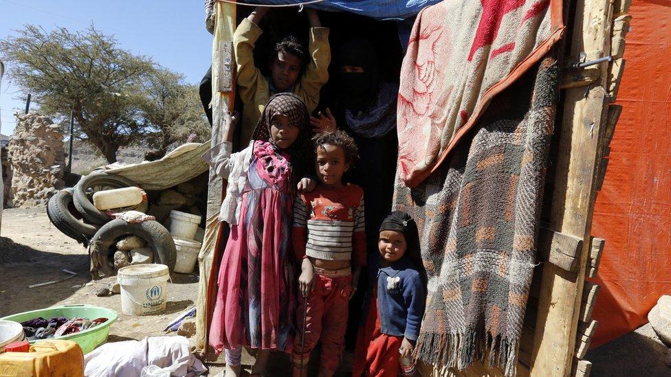 أطفال يقفون أمام خيمة تؤويهم في اليمن