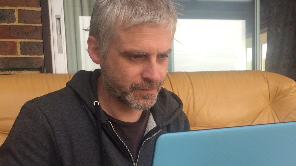 Iain Taylor sentado frente a su laptop