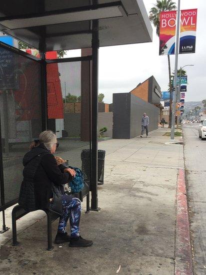 Una mujer sin casa en una parada de autobús en Los Ángeles