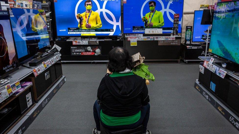 Uma mulher assiste aos jogos das Olimpíadas na televisão em uma loja