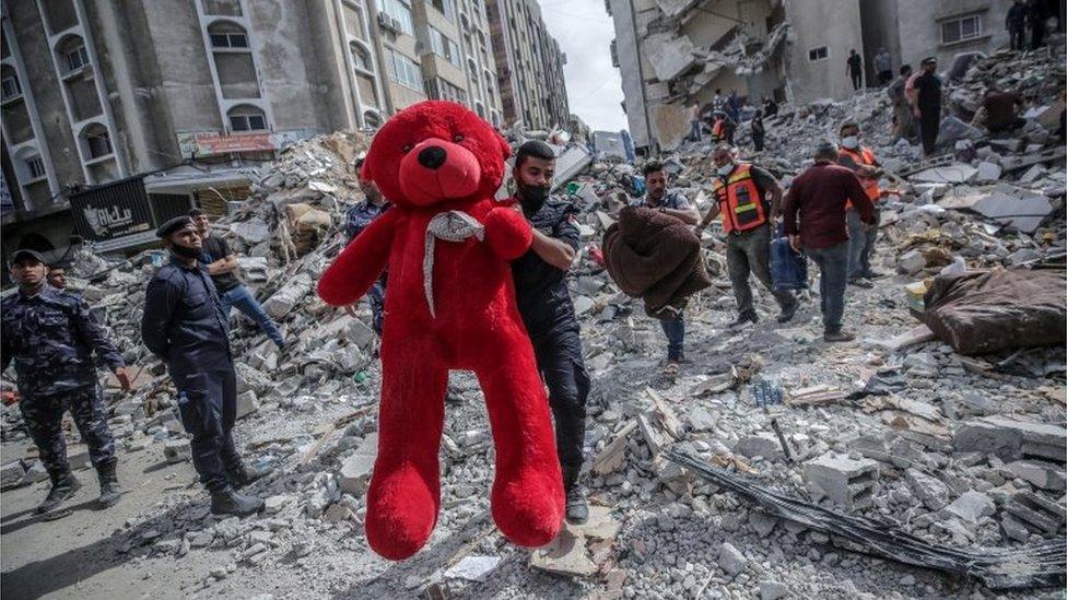 Un palestino con oso Teddy en medio de los escombros dejados por un ataque aéreo en Gaza.