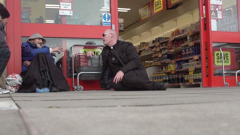Pastor Mick Fleming hablando con un hombre fuera de una tienda.