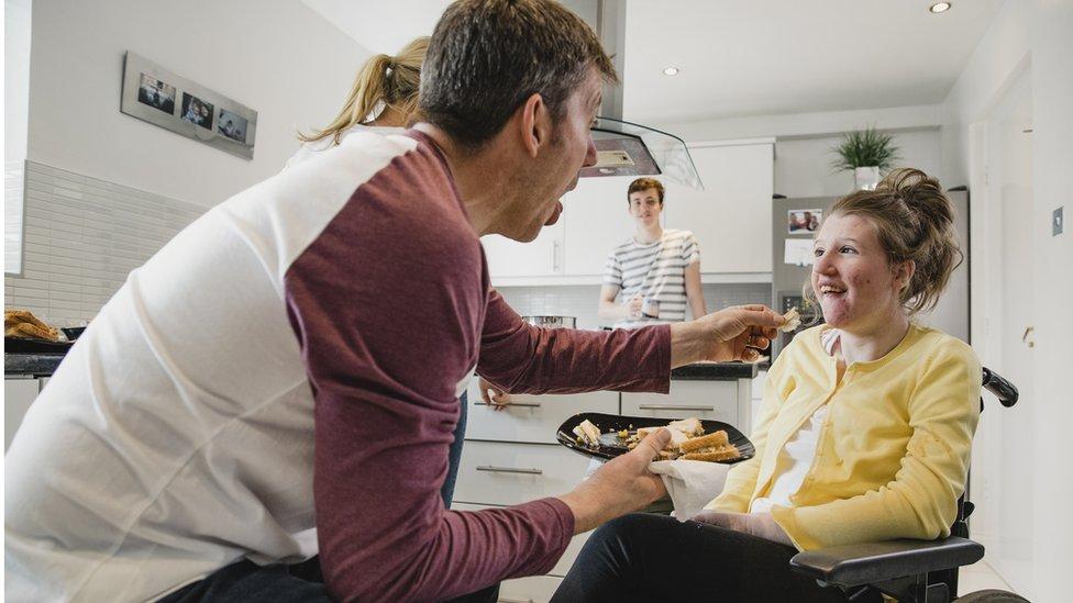Padre alimentando a su hija, con ELA.