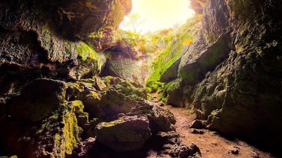 Pećina, a sunčevi zraci se prolamaju kroz ulaz u pećinu
