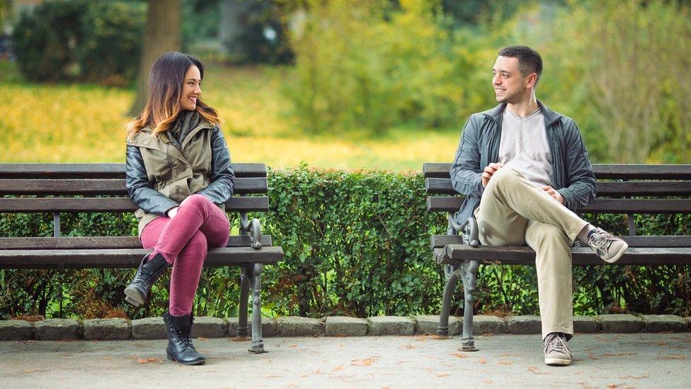 Un hombre y una mujer conversando sentados en dos bancas de un parque.