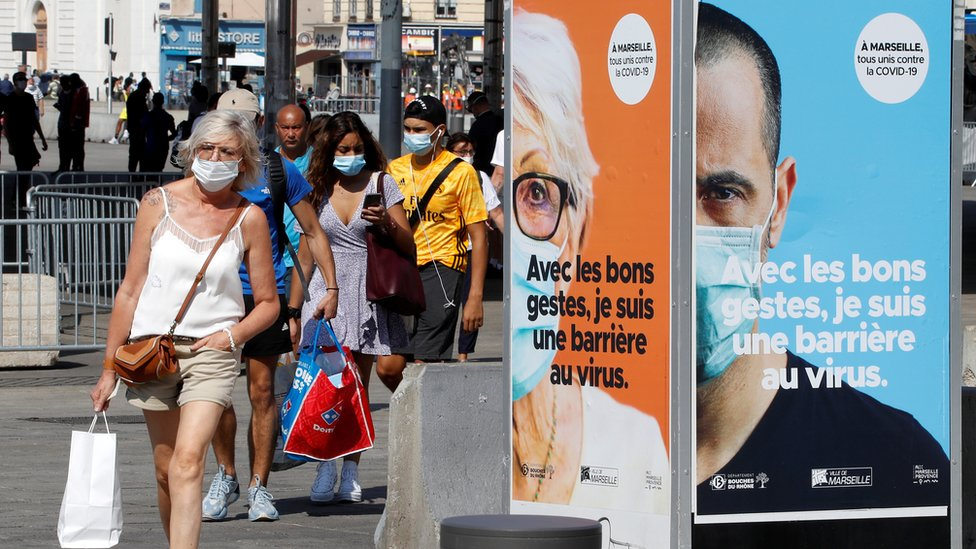 People wearing protective face masks walk near the Old Port (Vieux Port) in Marseille, France