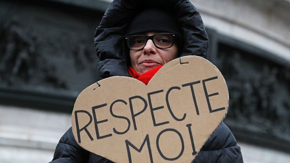 """Woman in hooded jacket holds a cardboard with the message """"respect me"""" in French"""