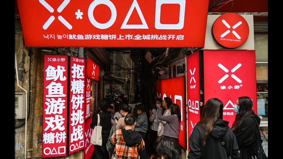 """Fila fuera de un comercio ambientado en """"El juego del calamar"""" en Shanghái."""