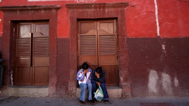 Mexican women sit outside a cantina