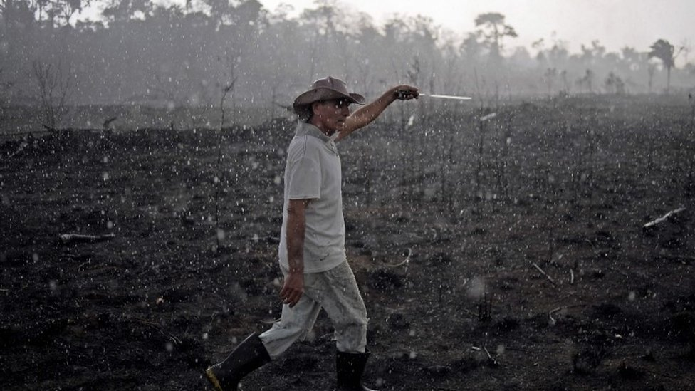 A Brazilian farmer walks through a burnt area of the Amazon in Rondonia state