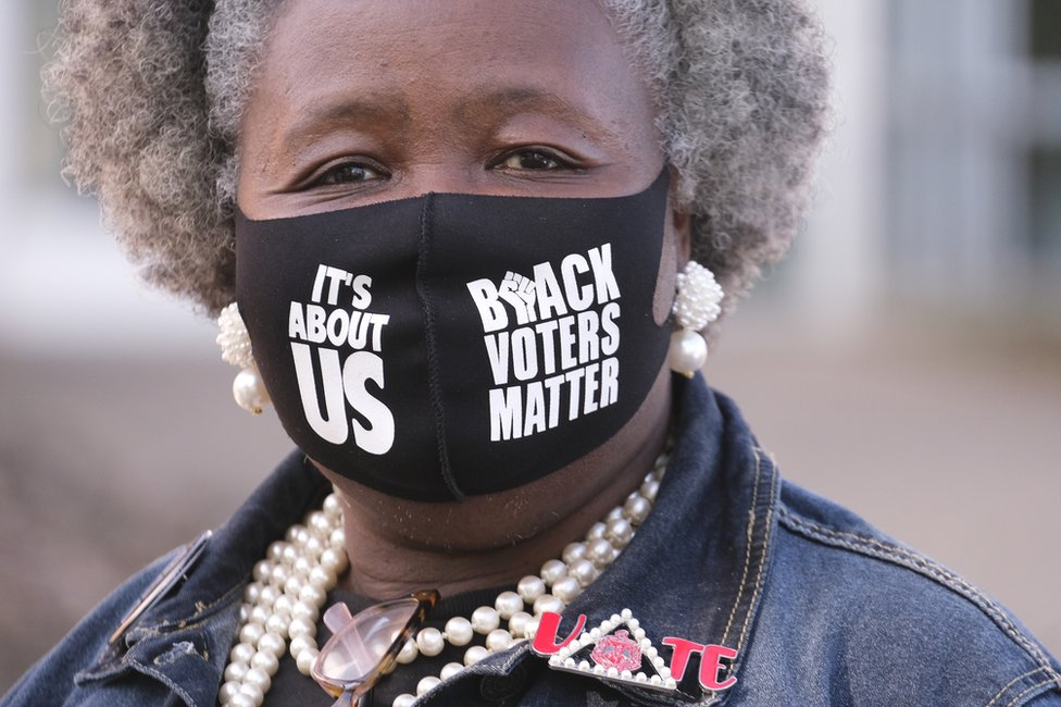 A woman wears a Black Voters Matter mask and looks to the camera