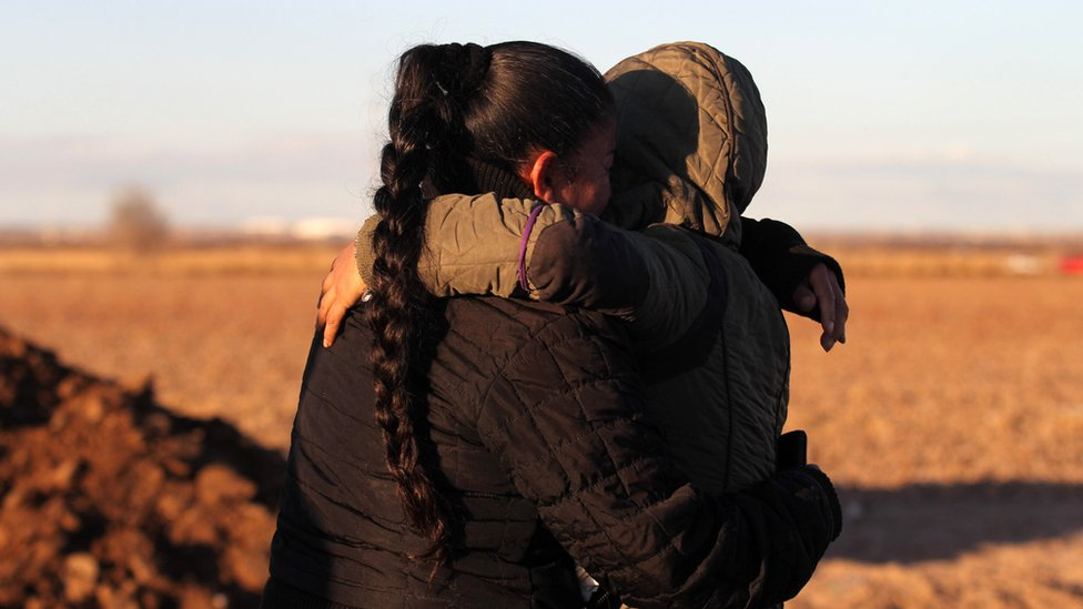 A woman and child hold each other near the US/Mexico border