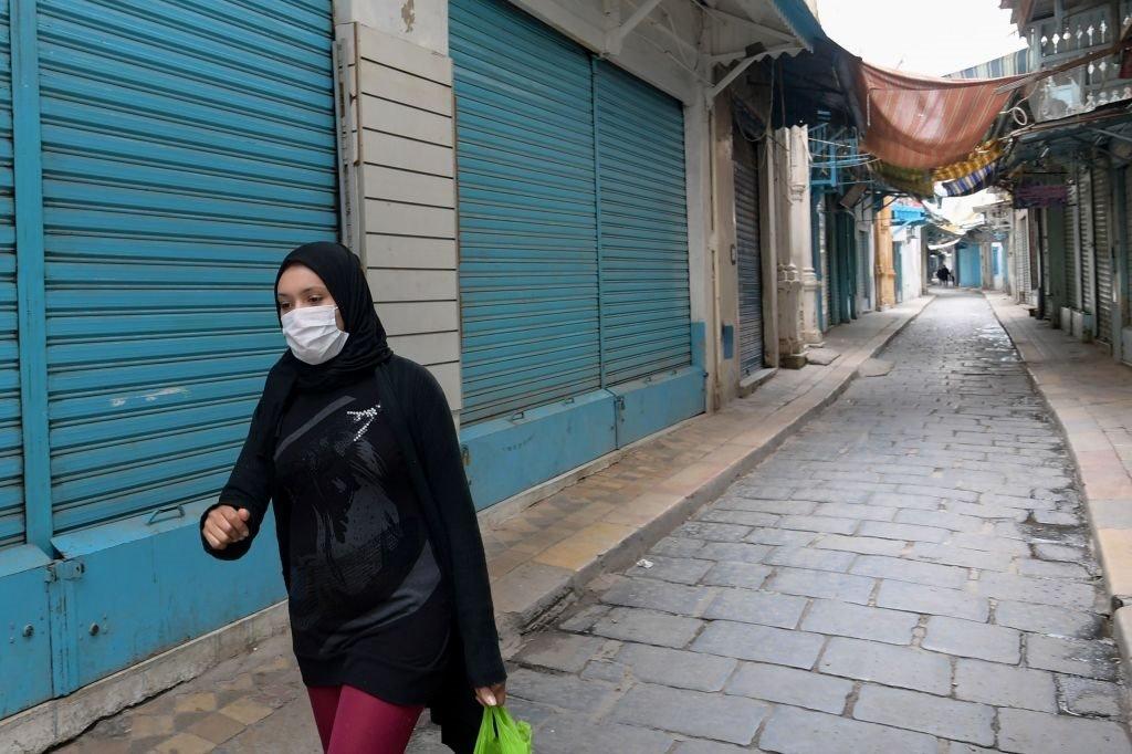 امرأة تونسية ترتدي قناع الوجه الطبي وتسير عبر زقاق خالٍ من الناس في سوق المدينة بتونس،