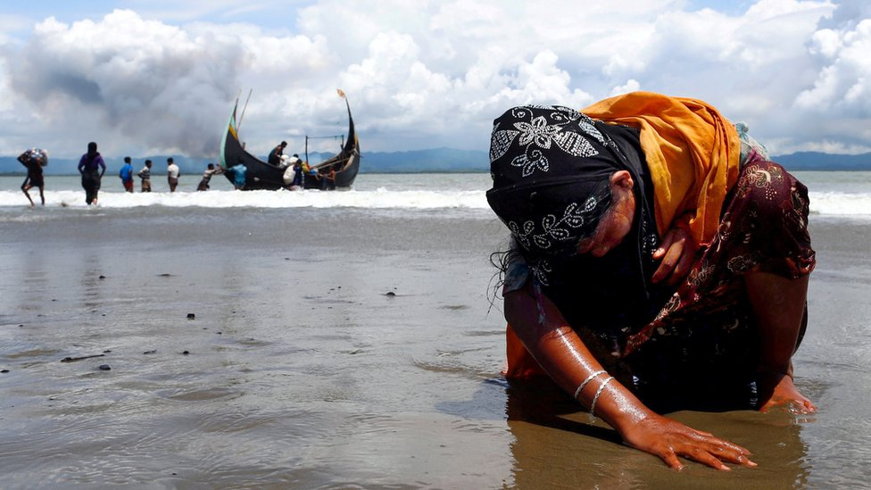 An exhausted Rohingya refugee woman touches the shore - September 2017