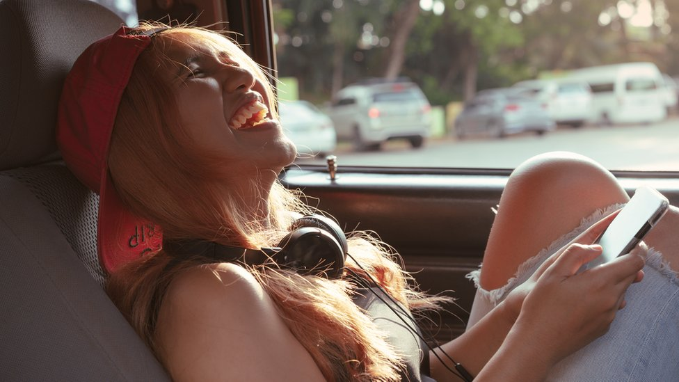 A woman, sitting in a car, laughing with a phone in her hand
