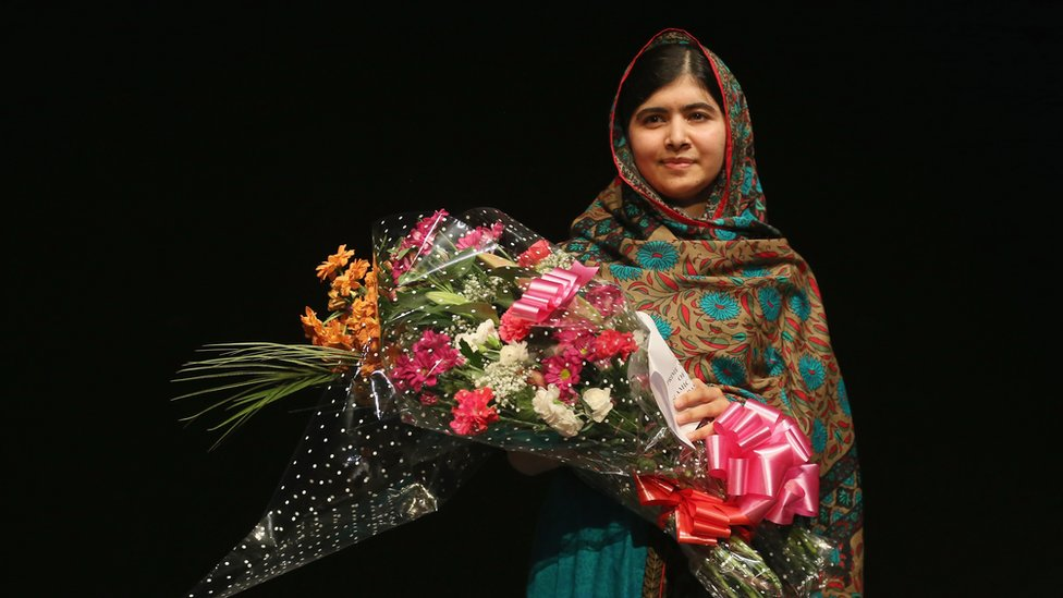 Malala Yousafzai photographed holding a bouquet of flowers on the day she was announced as a Nobel Laureate, 2014