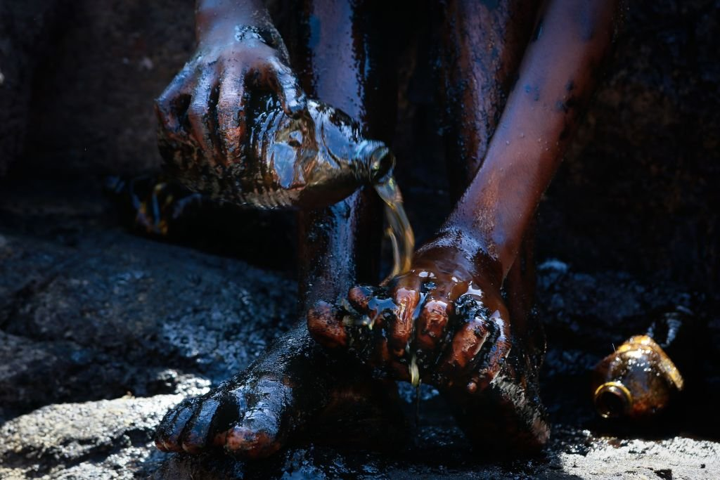 Una persona con manchas de petróleo se lava