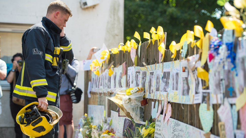 Firefighter looks at tributes during the silence