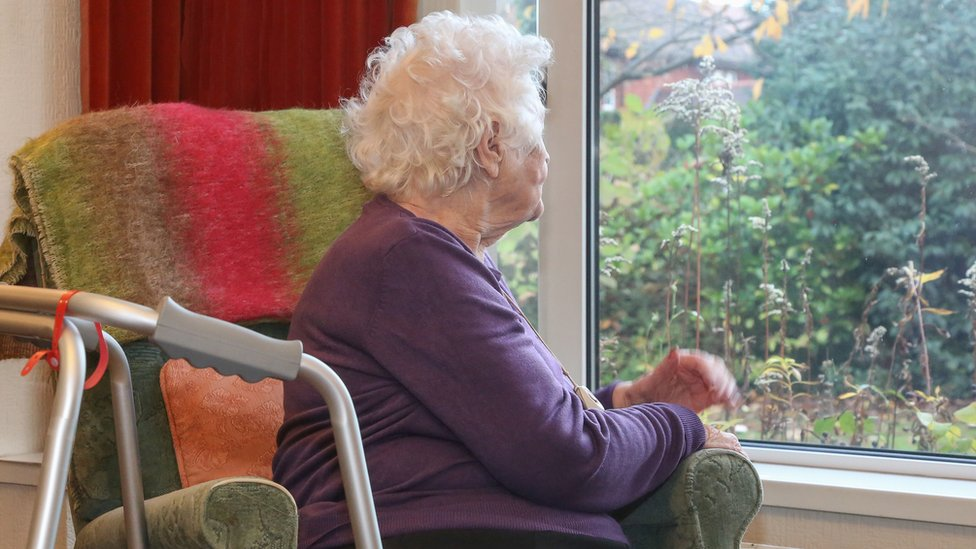 An old woman on her own looking out the window