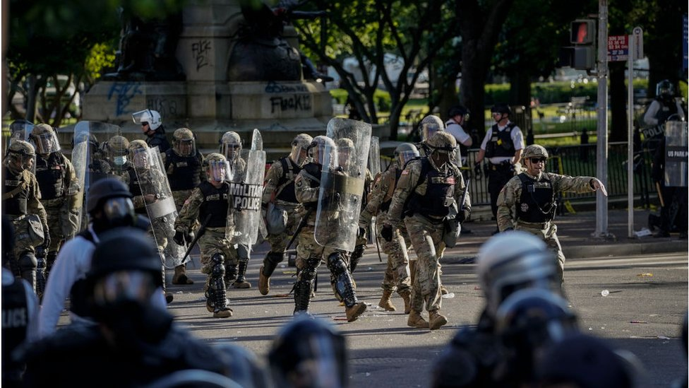 National Guard troops are seen moving behind the US Park Police