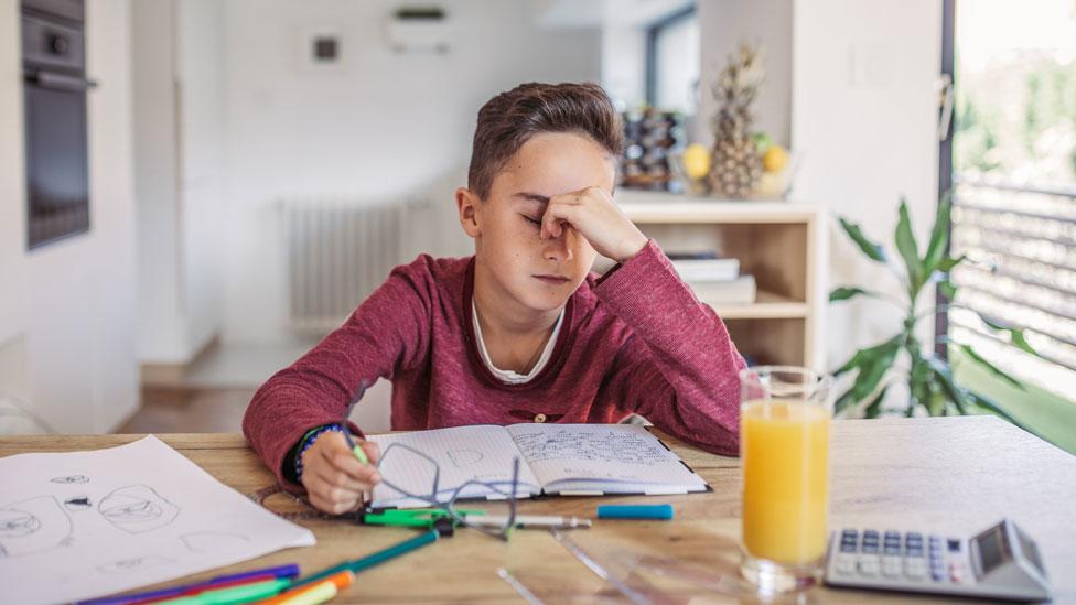Un niño que se toma la cara mientras estudia