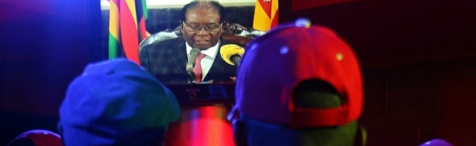 People watch as Zimbabwean President Robert Mugabe addresses the nation on television, at a bar in Harare, Zimbabwe, November 19, 2017.