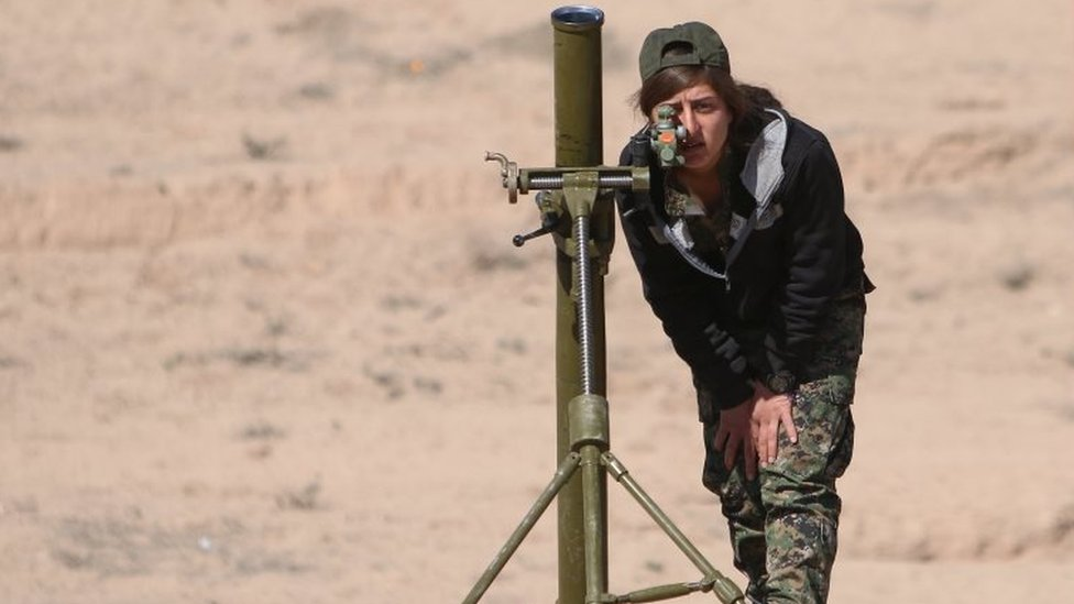 A Syrian Democratic Forces (SDF) female fighter adjusts a mortar in northern Deir al-Zor province ahead of an offensive against Islamic State militants, Syria on 21 February 2017.