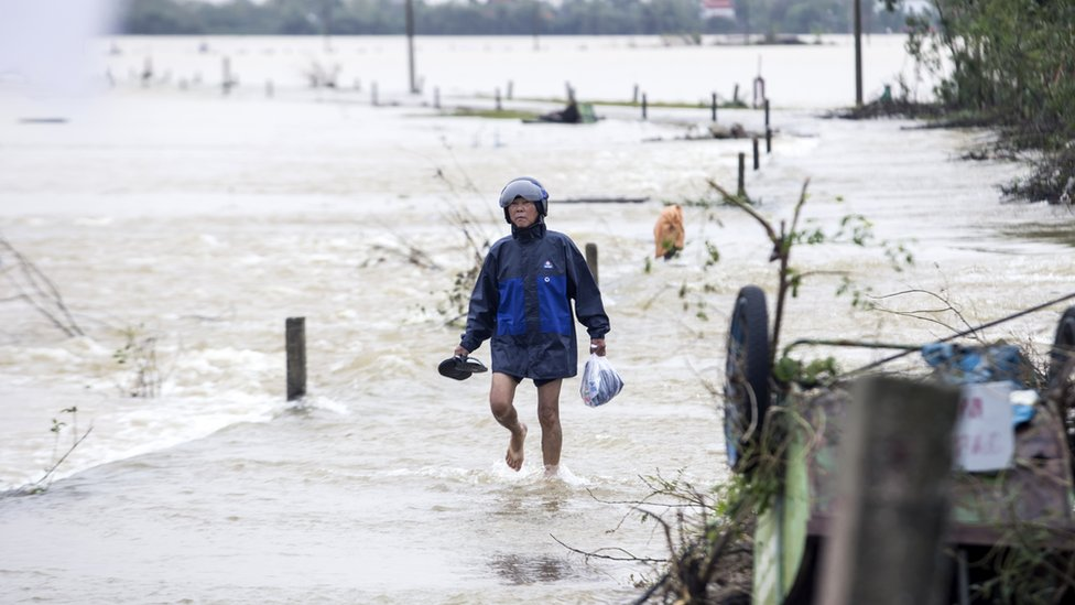 A local resident walks through the floodwater to a pick-up point for relief packages in Quang An Commune, Thua Thien Hue, Vietnam