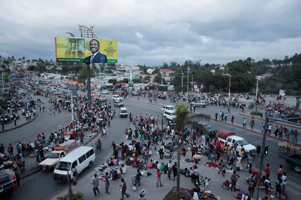 People walk in the street next to an electoral billboard of presidential candidate Jude Celestin in Port-au-Prince, Haiti, 17 November