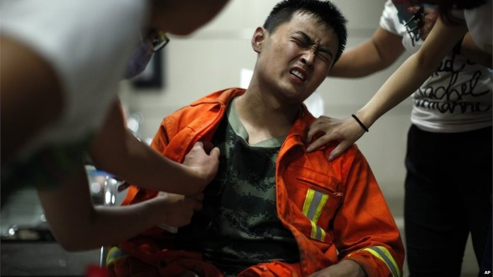 An injured firefighter grimaces as he is examined in a hospital following explosions in Tianjin municipality, Aug. 13, 2015