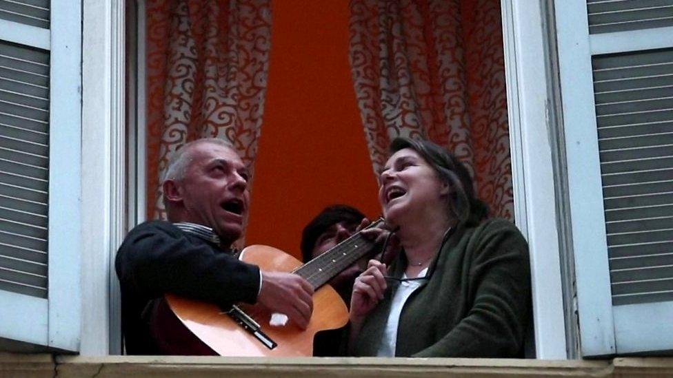 Hombre y mujer cantando desde una ventana en Italia