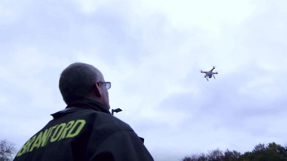 DJI drone being looked at by man