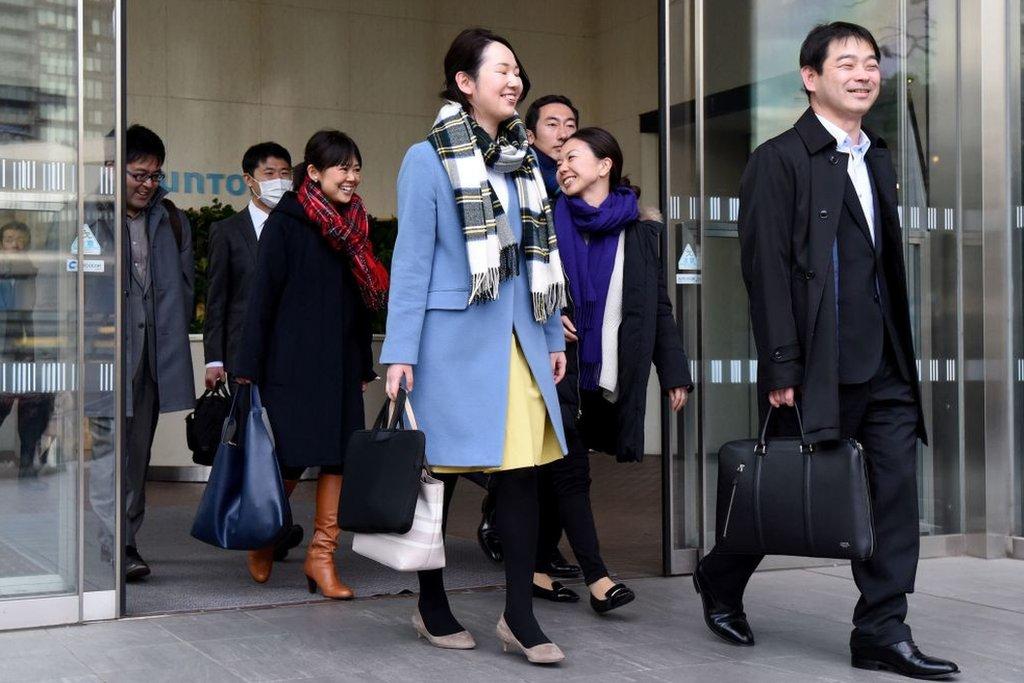 Trabajadores japoneses salen de la empresa sonriendo.
