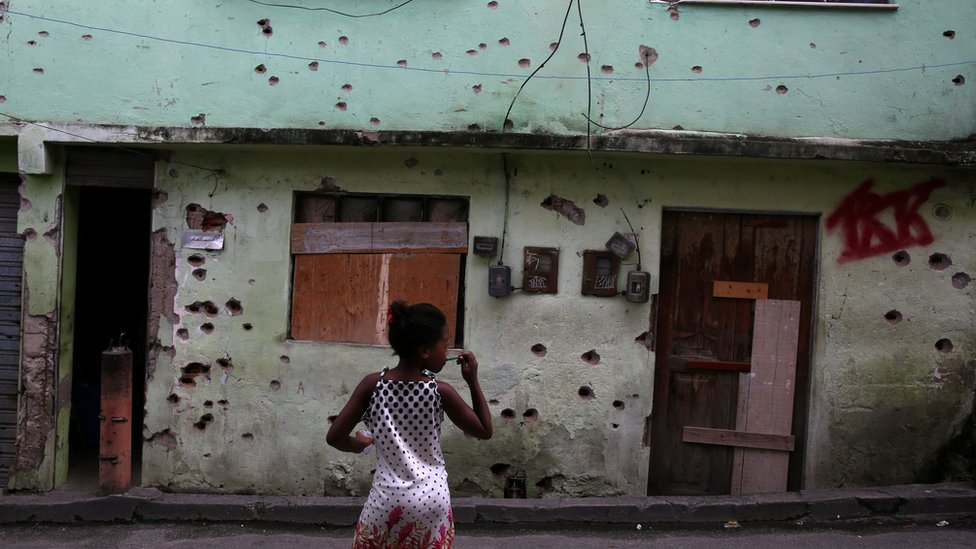 A girl stands in front of a house which is damaged by bullet holes in the Complexo de Alemao favela in Rio de Janeiro, Brazil