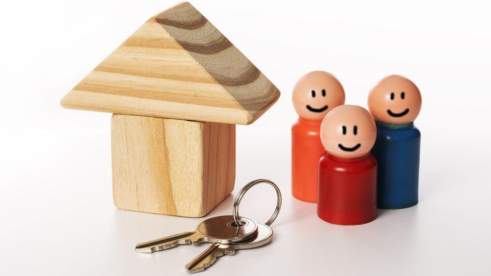 Model of house, keys and family
