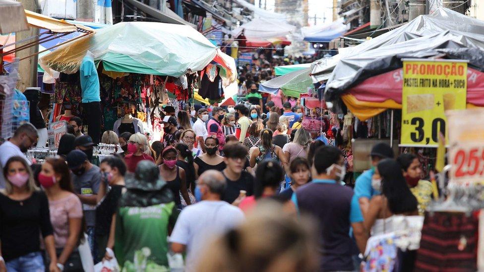Grando movimentação em rua de comércio popular em Manaus