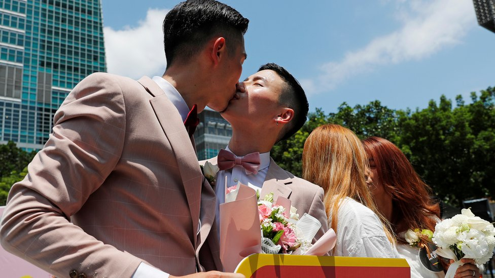 Couples kiss at a pro same-sex marriage party after registering their marriages in Taiwan