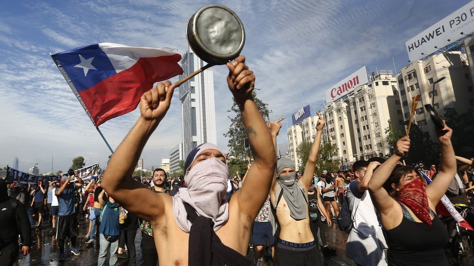 Demonstrators display flags and banners during a protest against President Sebastian Piñera on October 21, 2019 in Santiago, Chile