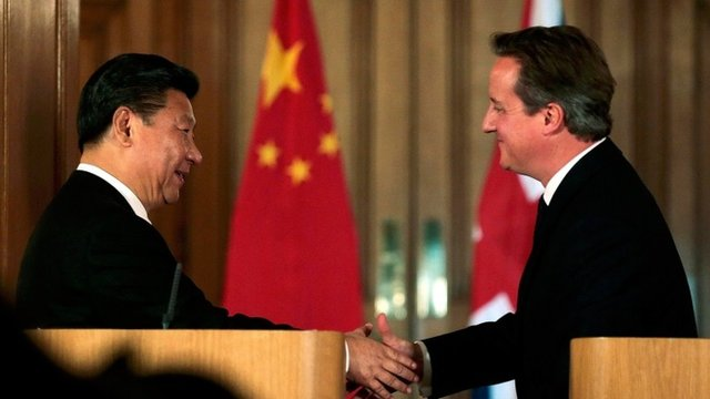 China's President Xi Jinping and Britain's Prime Minister David Cameron shake hands as they attend a joint press conference